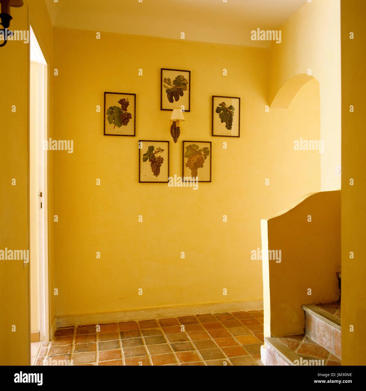 Yellow hallway with art on wall - Stock Image