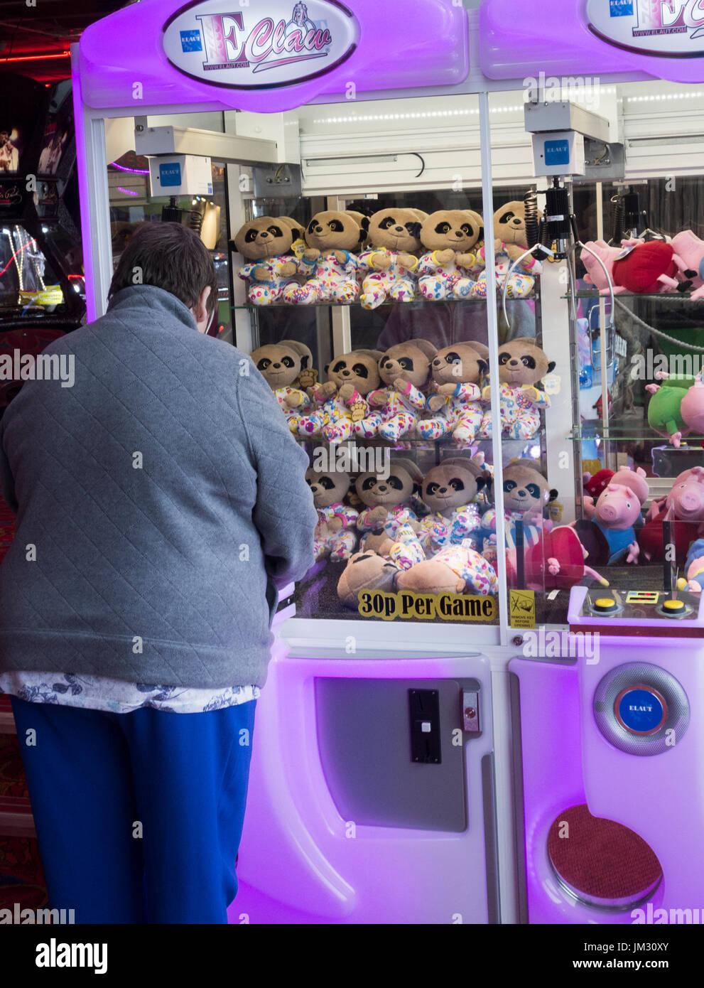 Woman playing on cran grab machine in seaside arcade. UK - Stock Image
