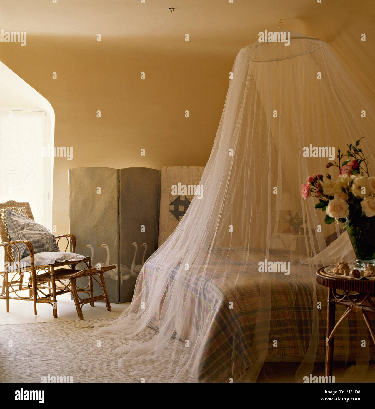 Country style bedroom with mosquito net - Stock Image