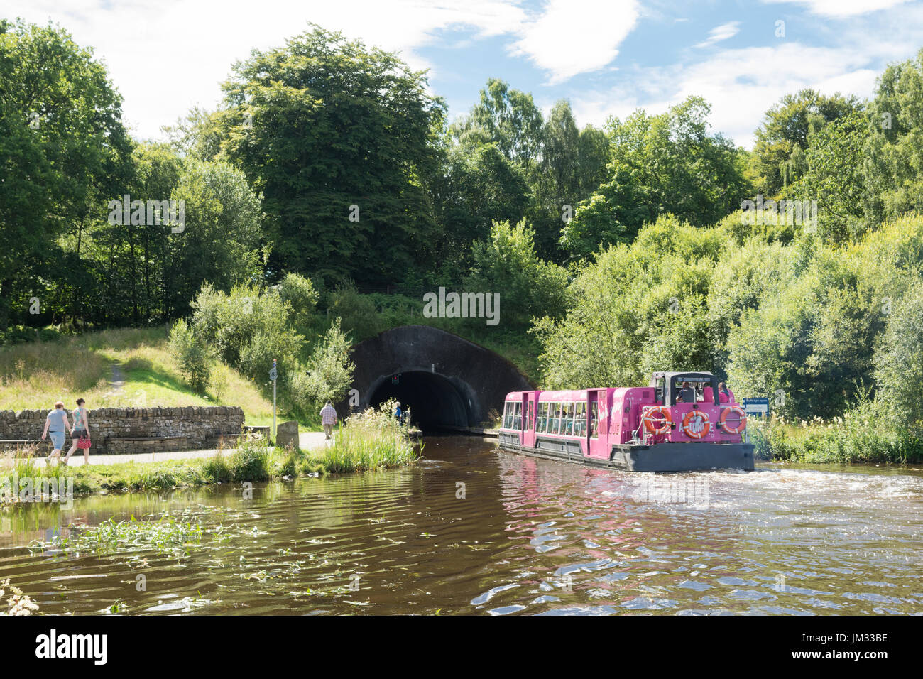 visitors on boat trip at the top of the Falkirk Wheel heading towards the tunnel and the Union Canal - Stock Image