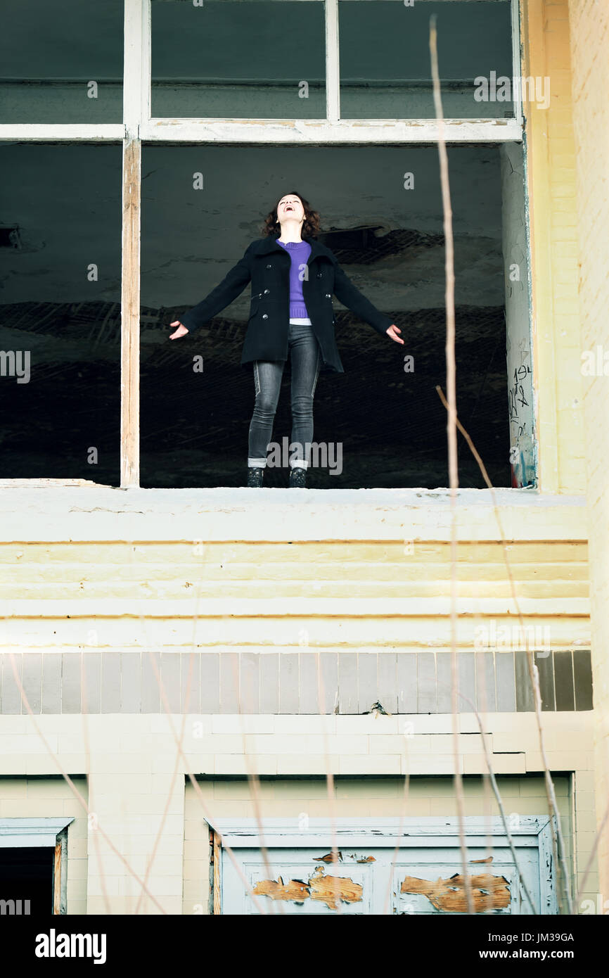 woman standing in the window - Stock Image