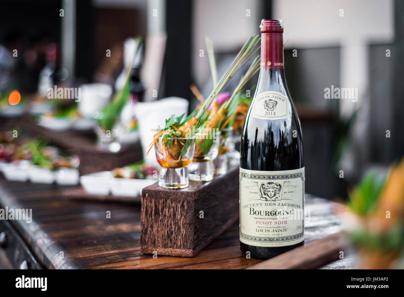 bottle of red bourgogne wine at oudoor party bar counter - Stock Image