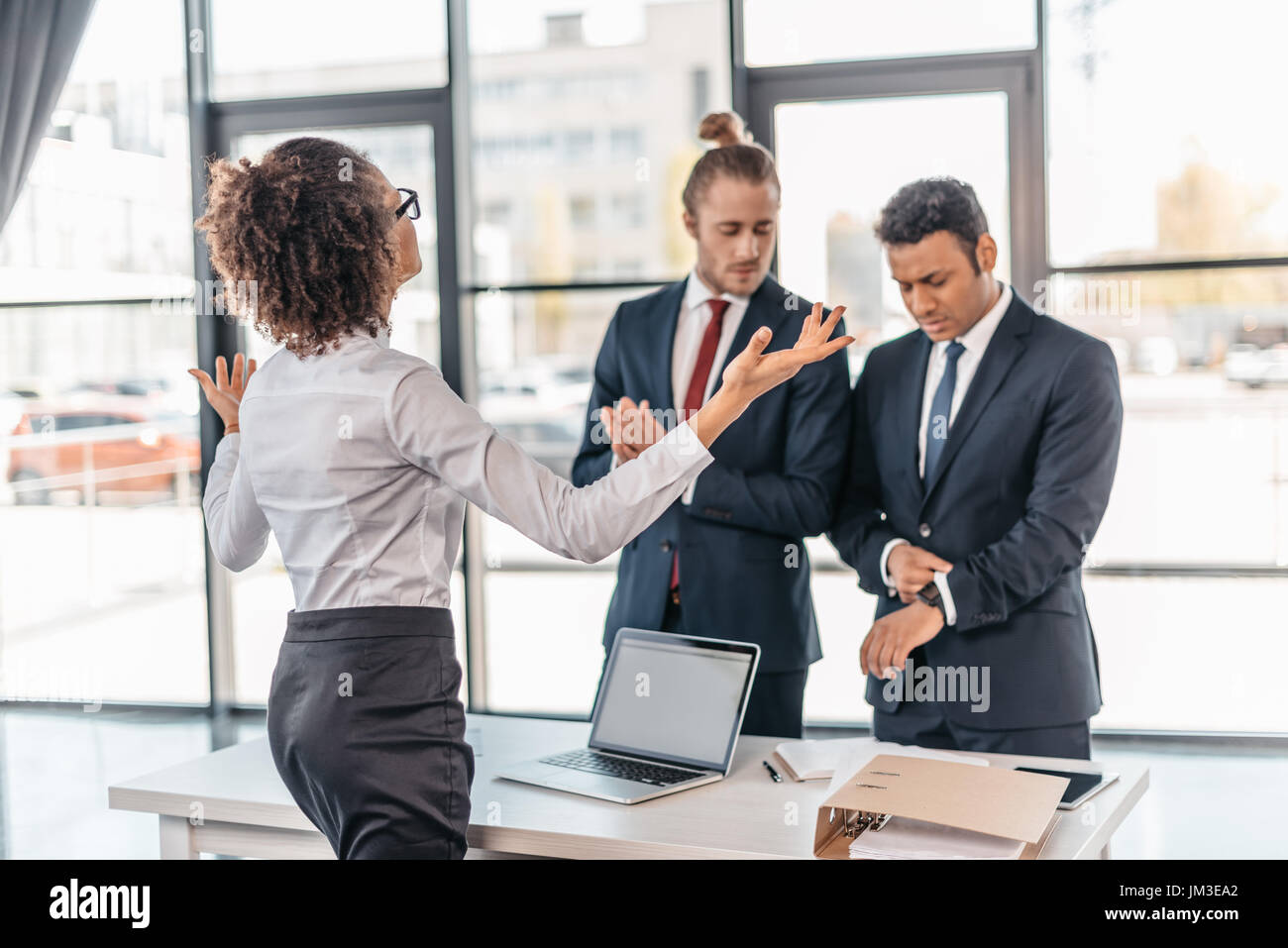 Young businesswoman gesturing and arguing with coworkers in office, business team meeting concept - Stock Image