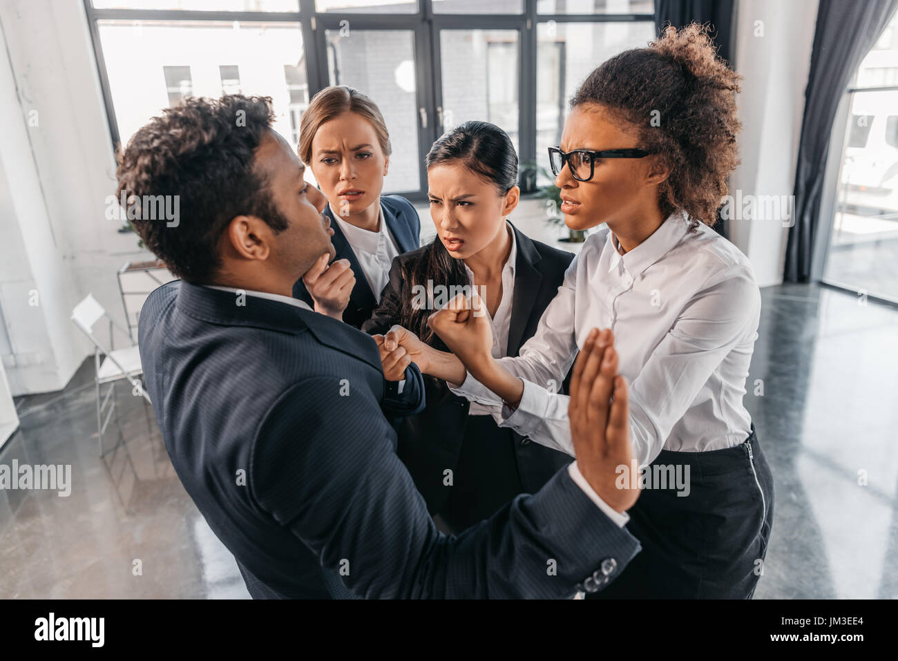 young emotional businesspeople in formalwear quarrelling at modern office, business team meeting - Stock Image