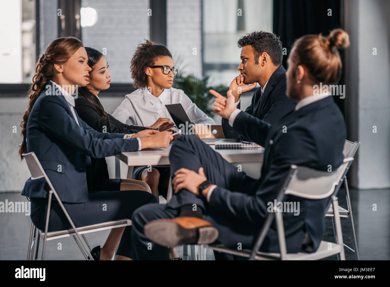 young coworkers in formalwear arguing at business meeting in office, business team meeting - Stock Image