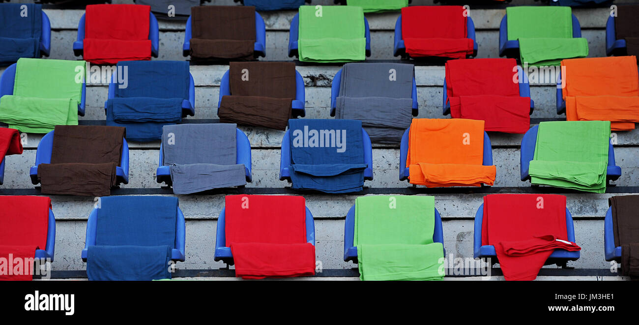 Unoccupied blue stadium chairs covered with colorful blankets - Stock Image