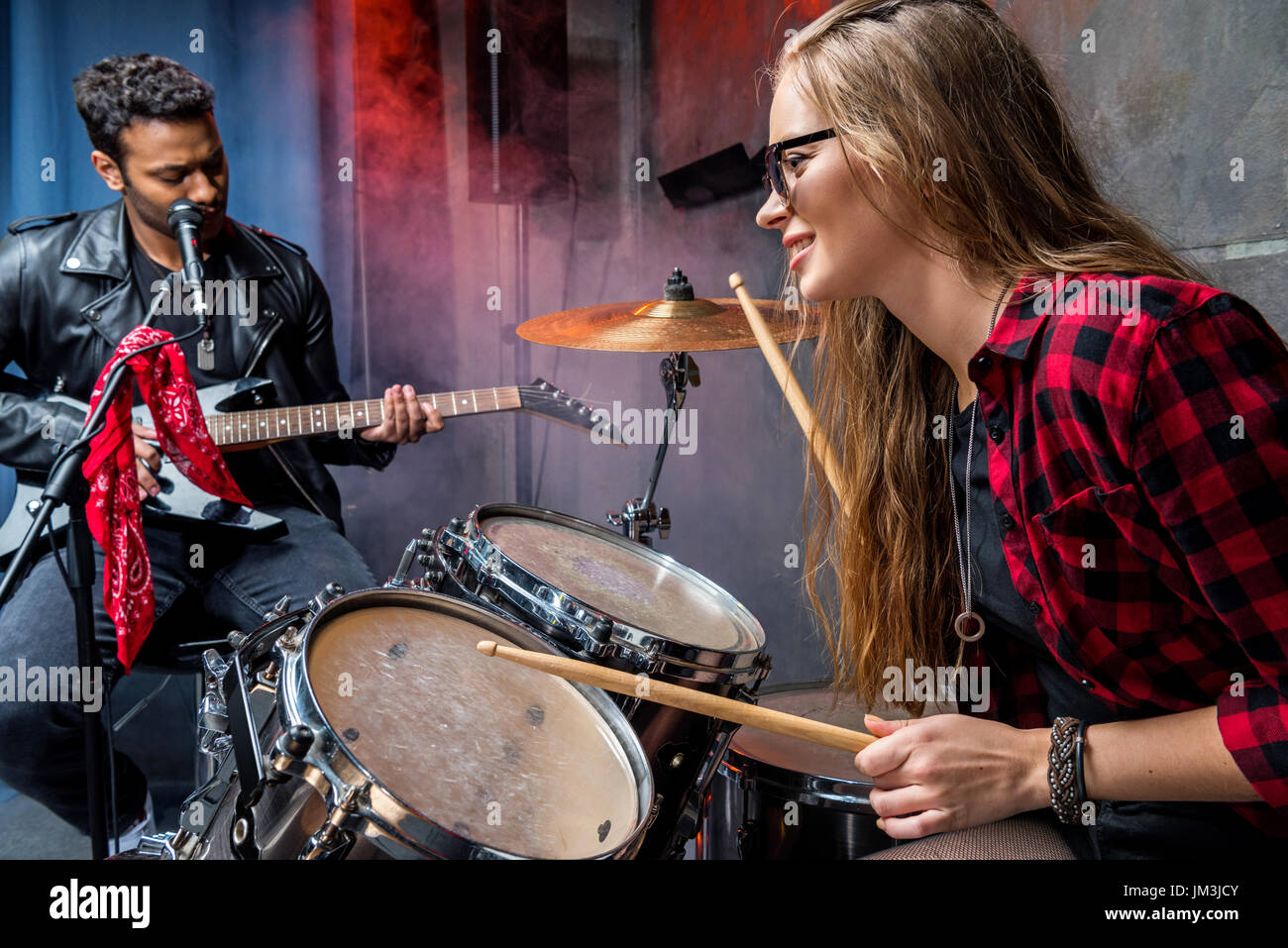 side view of woman playing drums with man playing guitar, rock band concept - Stock Image