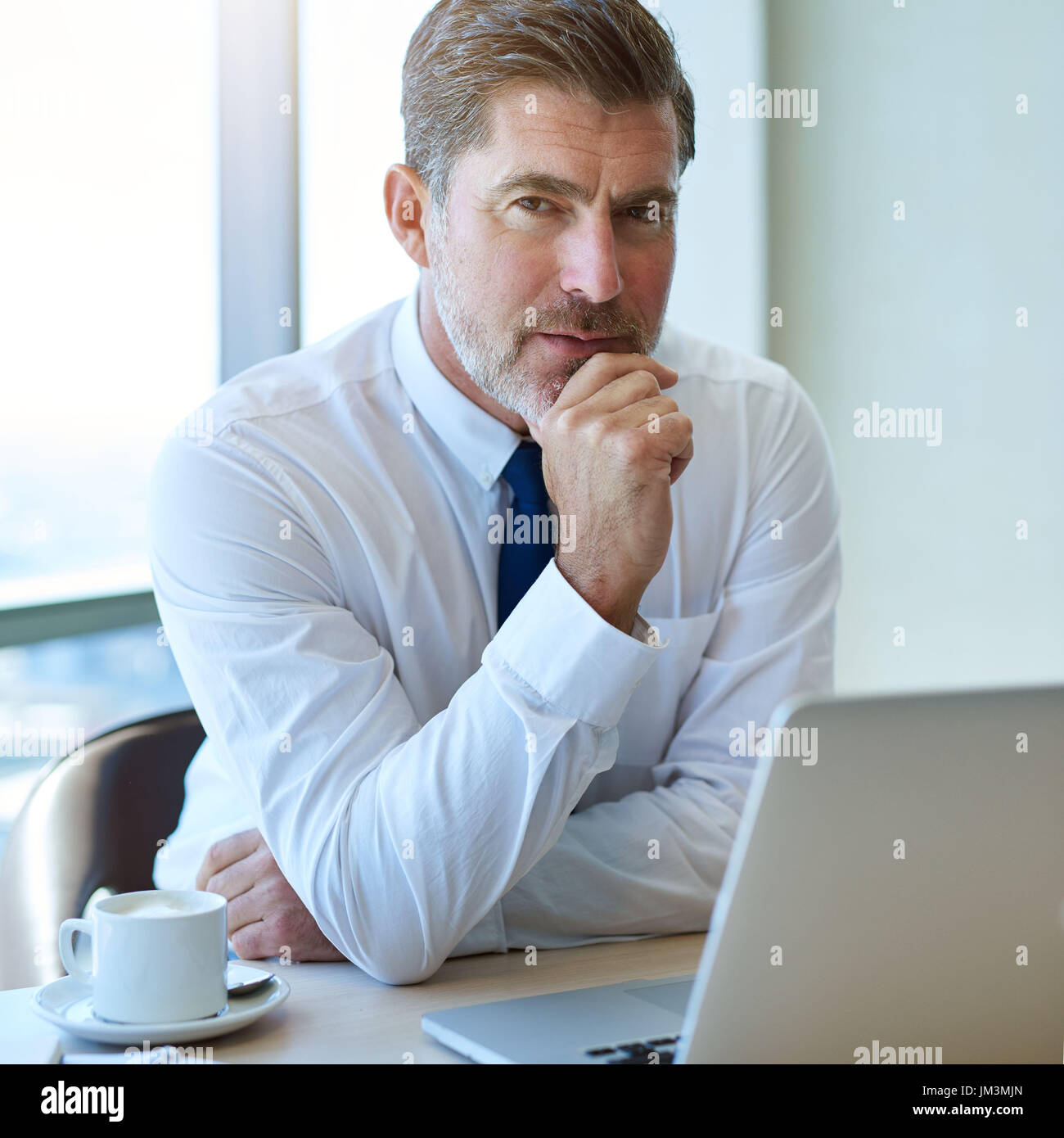 Portrait of a handsome mature business leader with greying hair and attractive short beard, sitting at this desk with a laptop and looking at the came - Stock Image