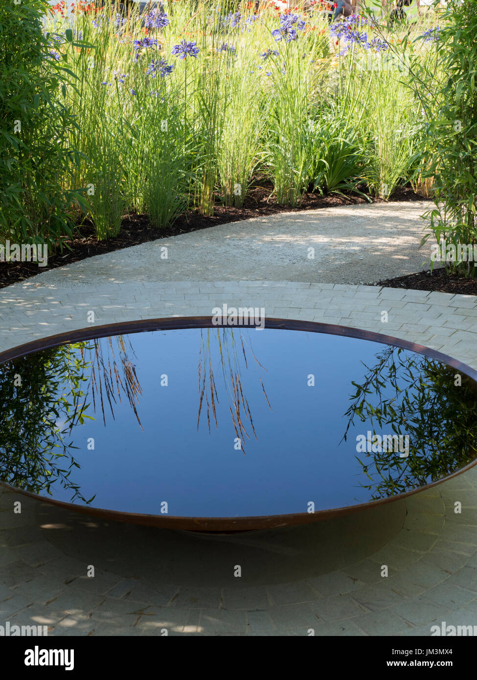 Hampton Court Show Garden - Perennial Sanctuary Garden designed by Tom Massey.  Silver Gilt medal.  Circular water pool / feature in the central paved - Stock Image