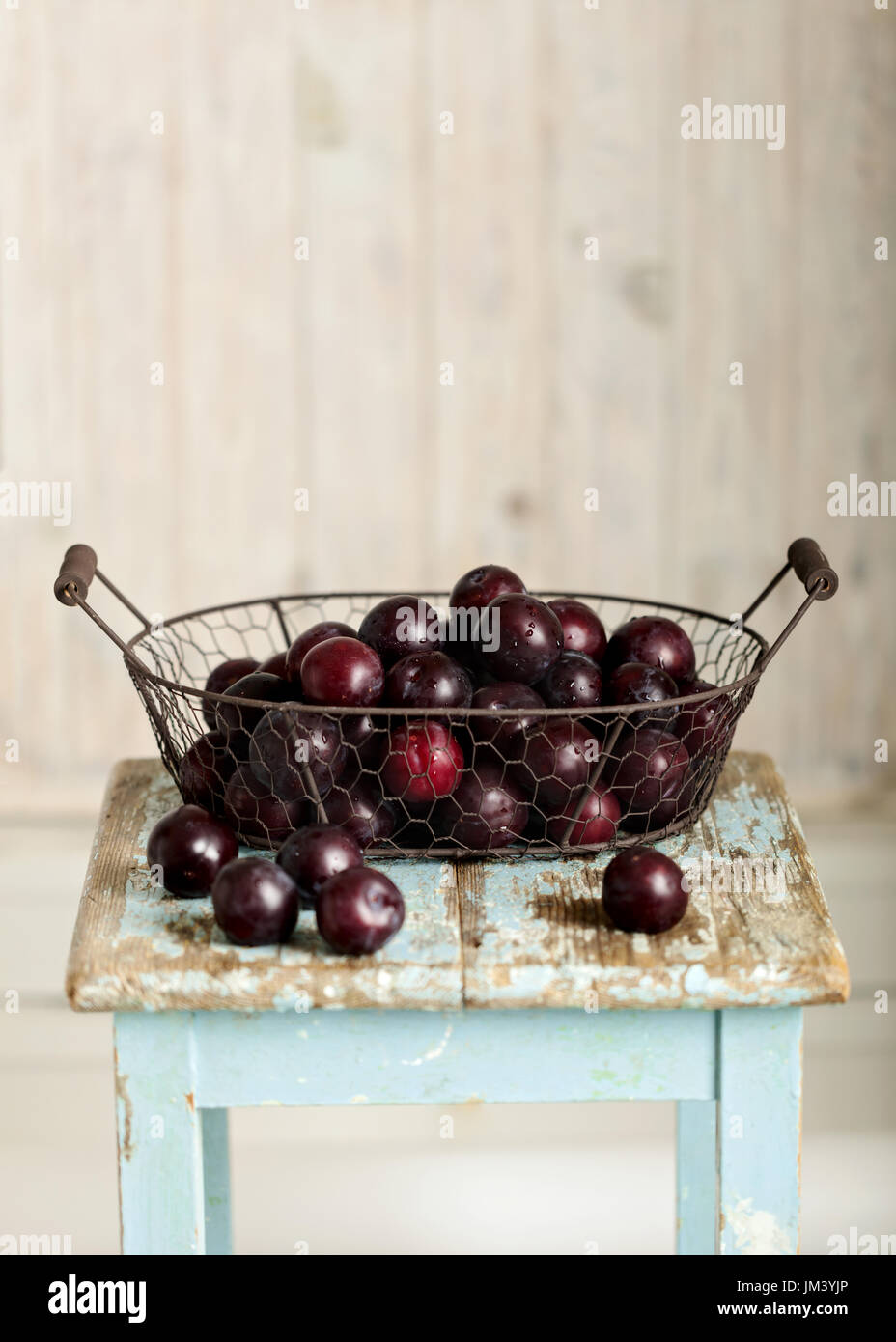 Ripe plums in a basket on a wooden background. Selective focus. Stock Photo
