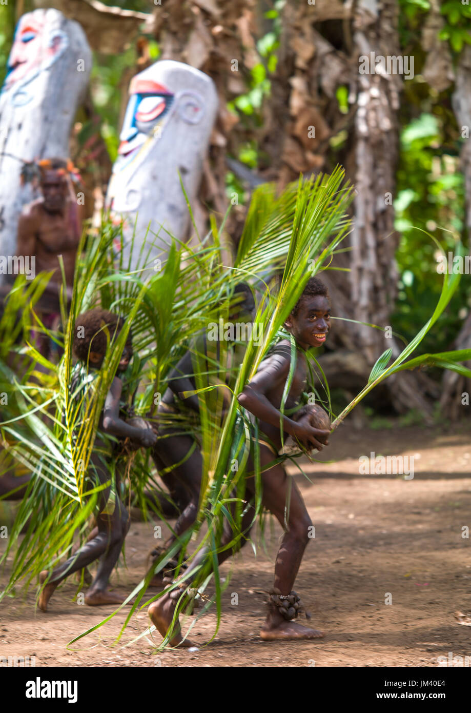 Small Nambas children covered with palm leaves dancing in front of slit gong drums during the palm tree dance, Malekula island, Gortiengser, Vanuatu - Stock Image