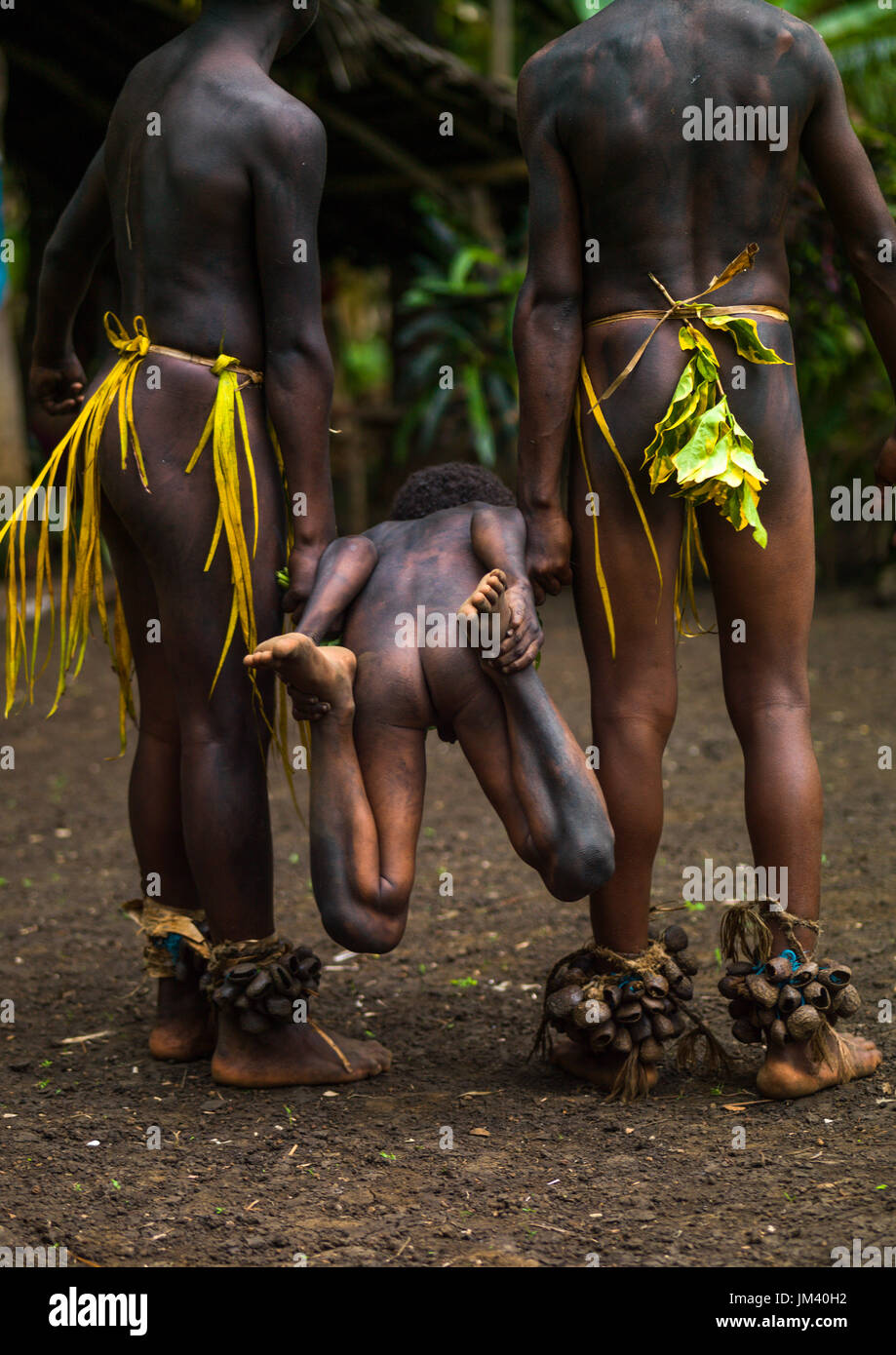 Small Nambas tribesmen demonstrating with a child a traditional stretcher made from leaves, Malekula island, Gortiengser, Vanuatu - Stock Image