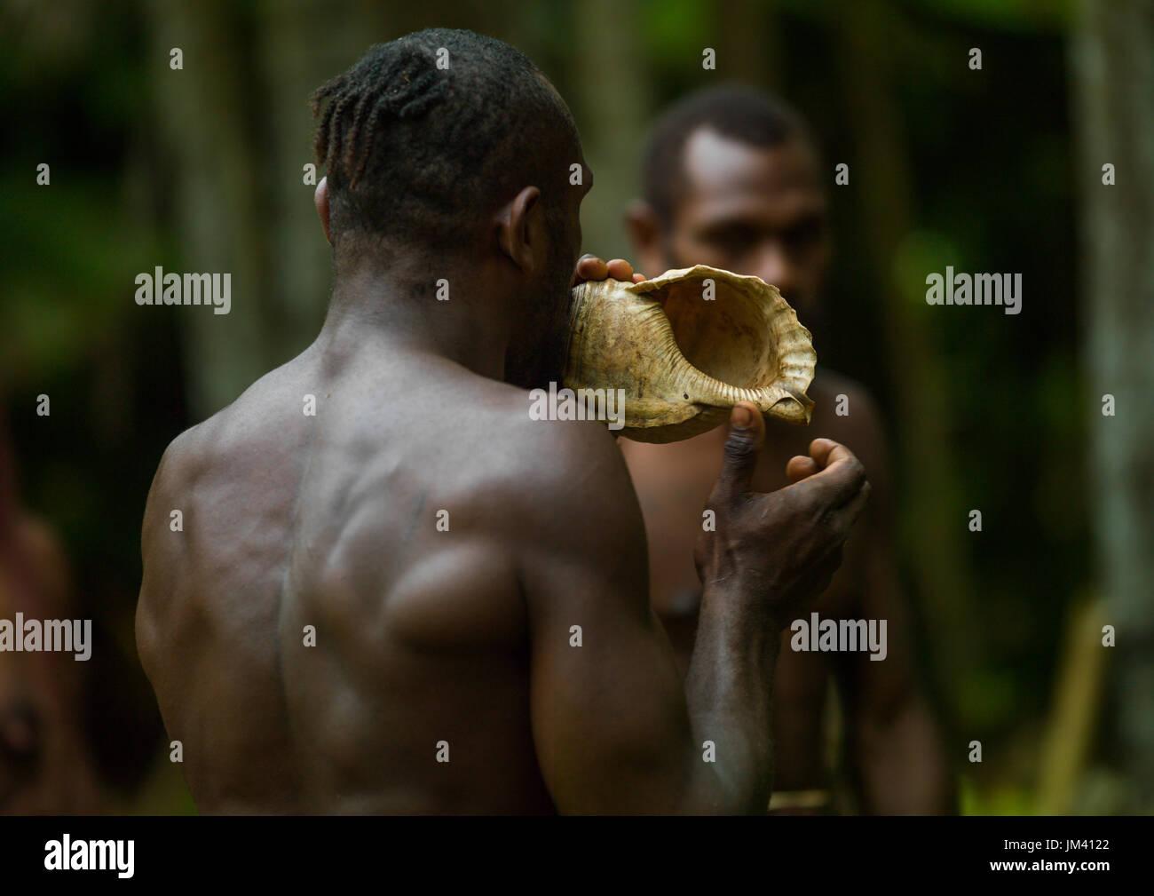 Big Nambas tribesman blowing in a shell, Malampa Province, Malekula Island, Vanuatu - Stock Image