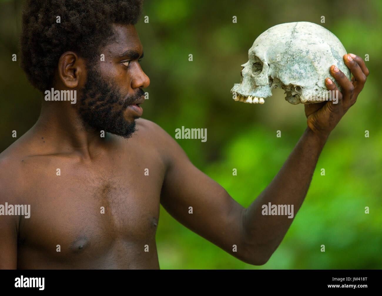 Man holding a human skull in Amelbati cannibal site, Malampa Province, Malekula Island, Vanuatu - Stock Image