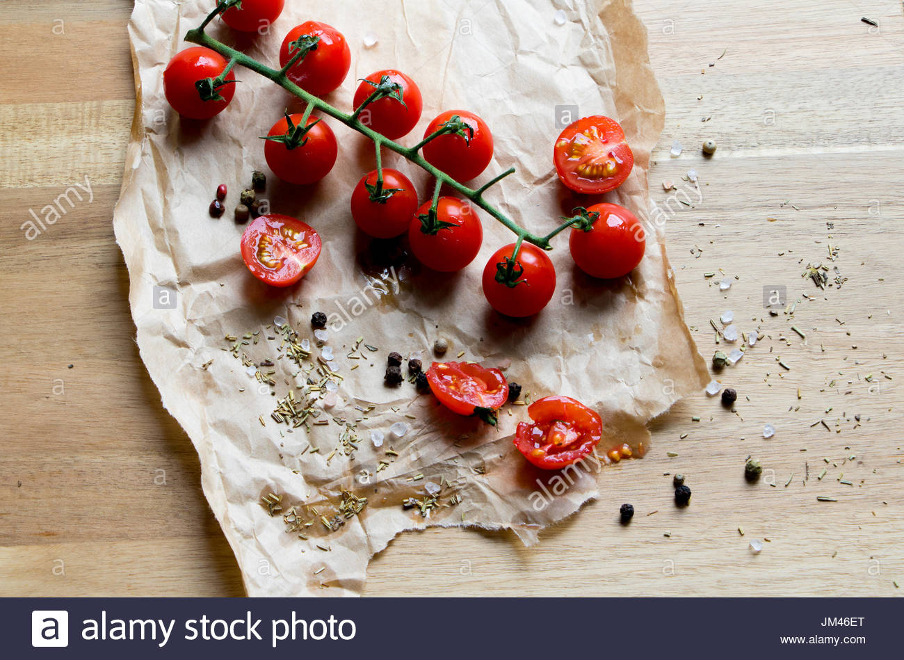 Food cherry tomatoes on brown paper wooden chopping board red tomatoes halved tomatoes patch, lunch break rustic image - Stock Image