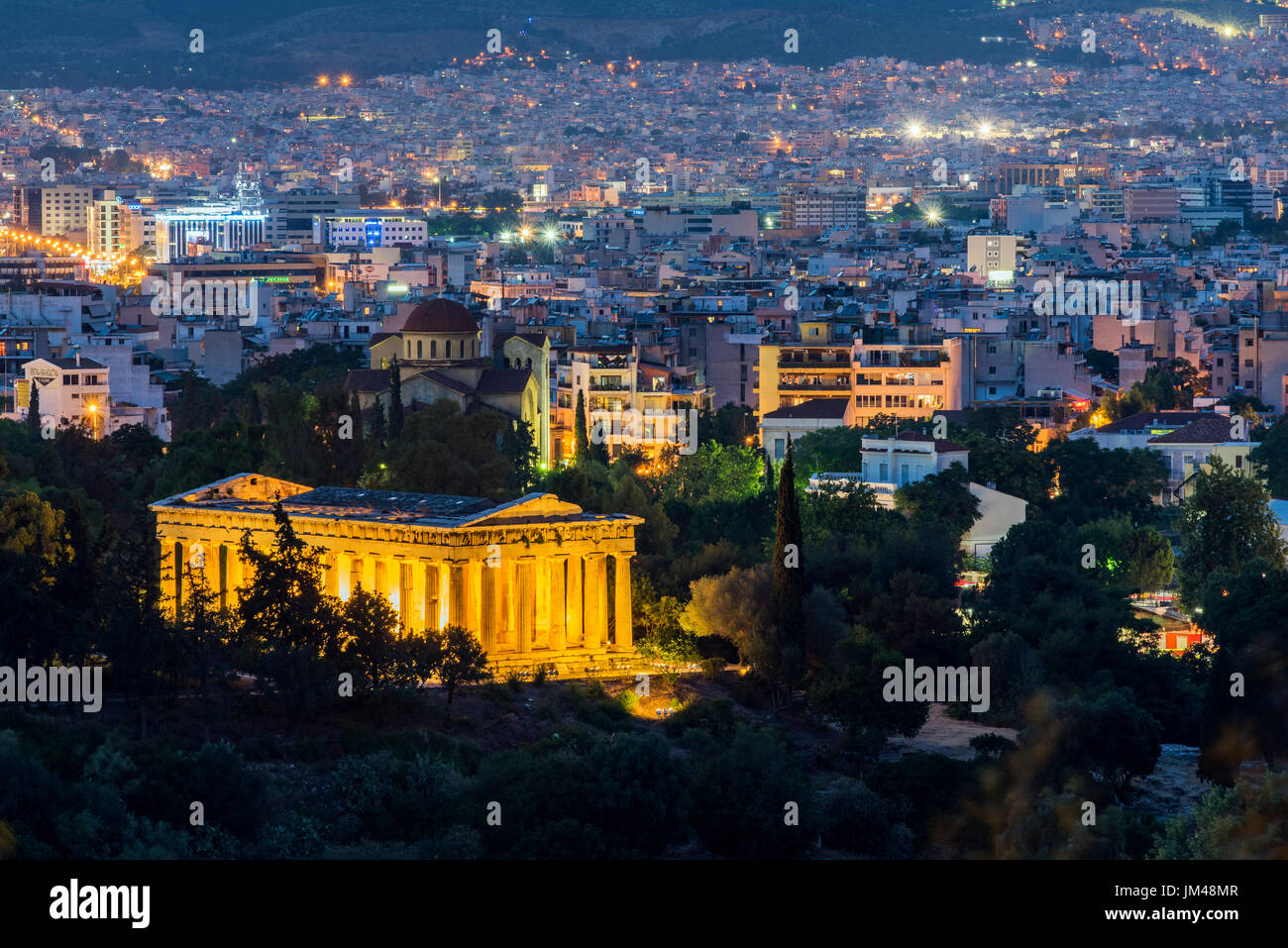 Night view of Temple of Hephaestus and city skyline behind, Athens, Attica, Greece - Stock Image