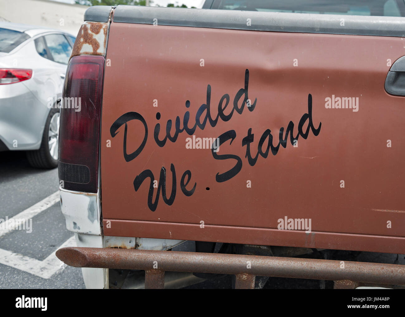 Divided We Stand written on back taligate of a pickup truck. - Stock Image