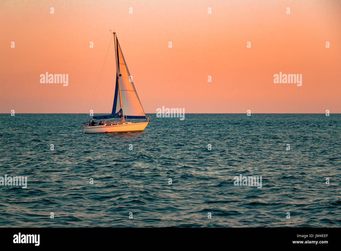 Sailing The Pacific Blue, sunset with calm waters, Dana Point California - Stock Image