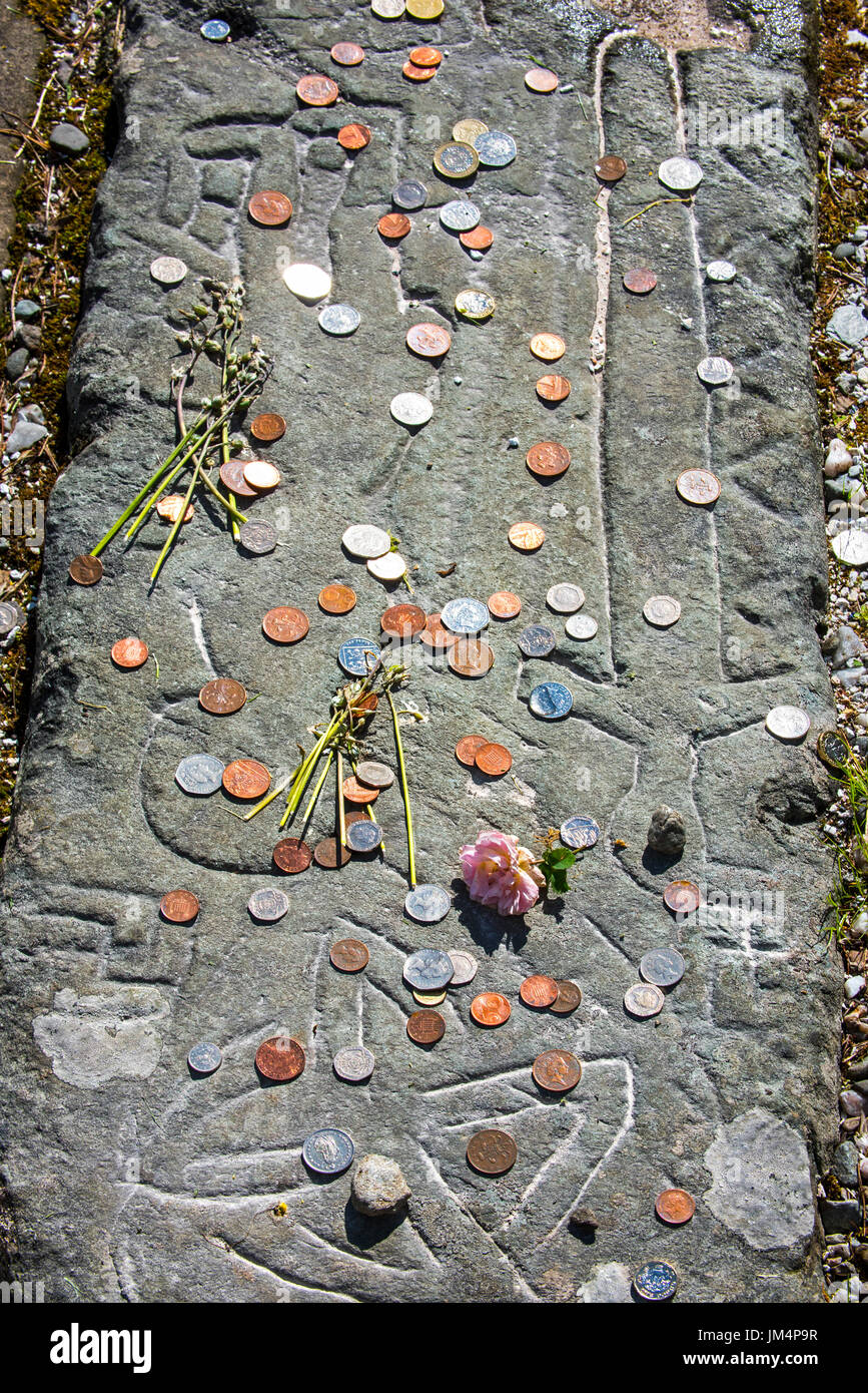 Coins on tombstone marking the grave of Rob Roy MacGregor at the Balquhidder kirkyard, Stirling, Scotland, UK Stock Photo