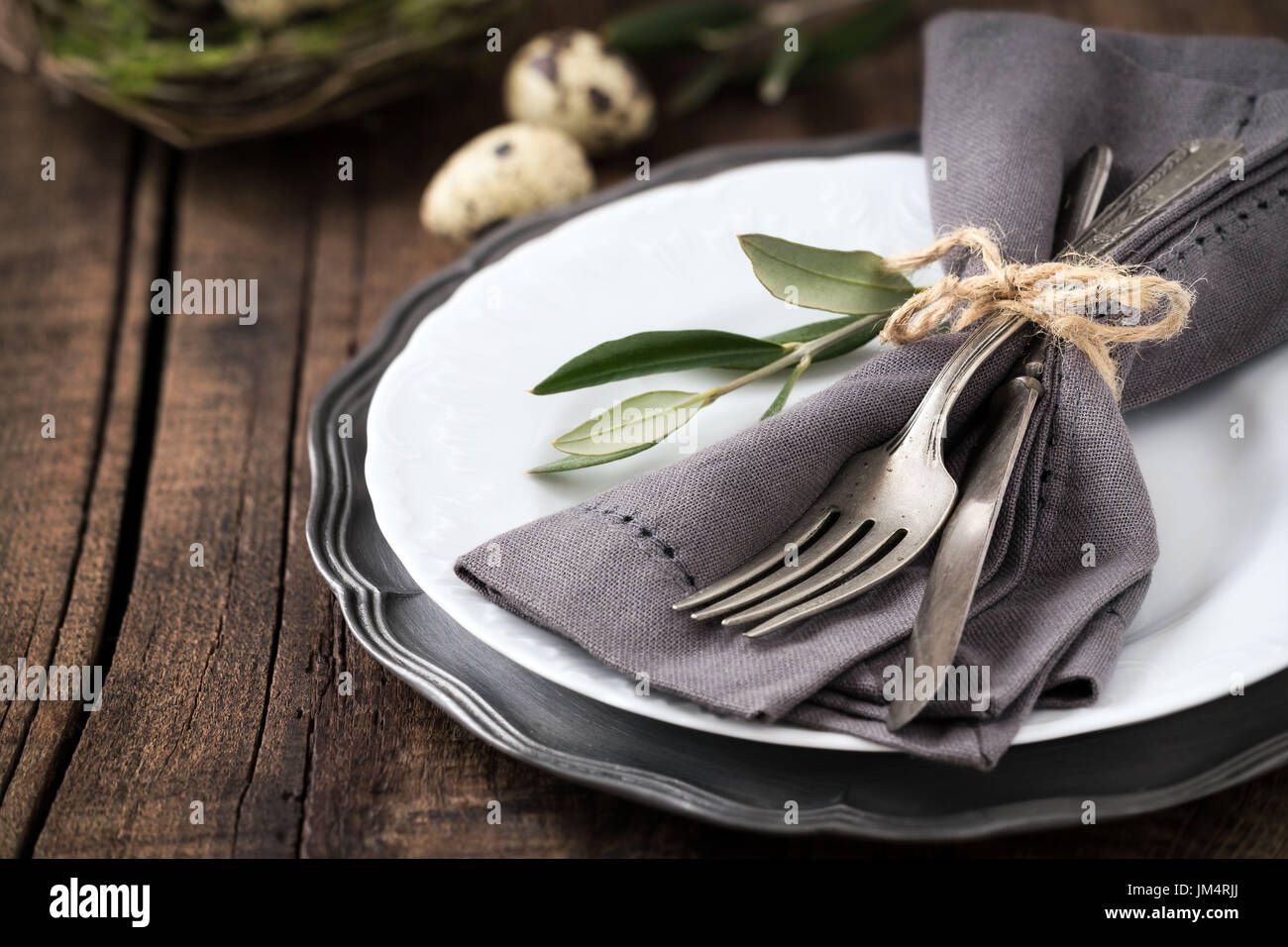 Easter table setting with vintage silverware with an olive branch on ...