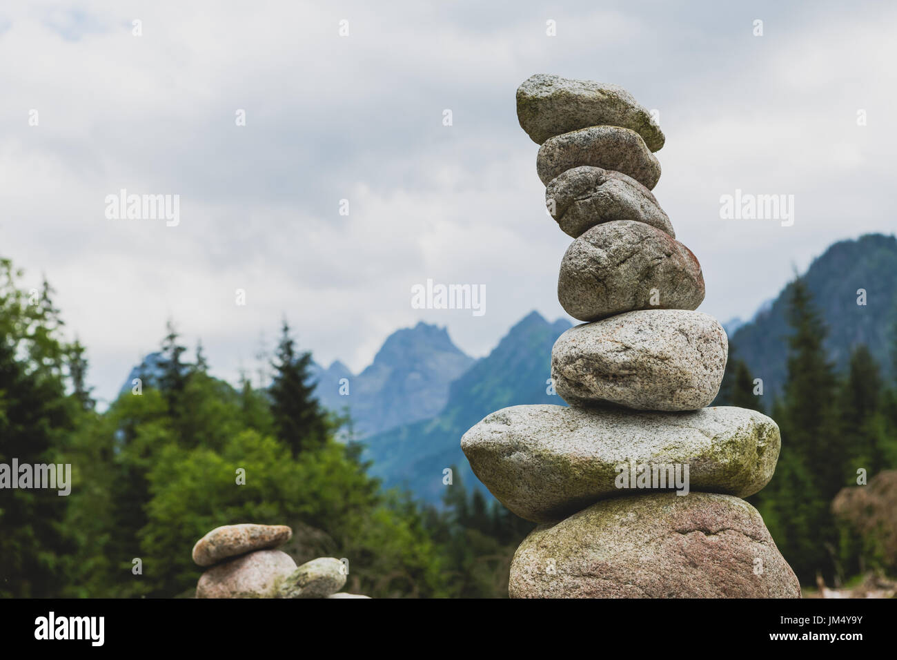 Stones balance, hierarchy stack over cloudy sky in mountains. Inspiring stability concept on rocks. - Stock Image