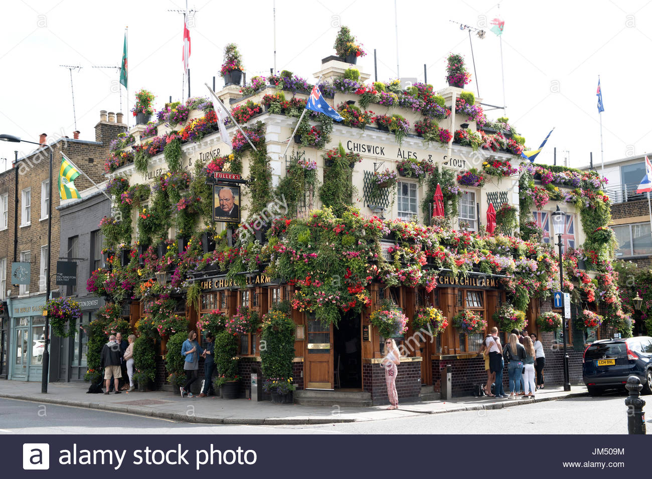 The Churchill Arms pub in Kensington, London in full Bloom with over a hundred hanging baskets, window boxes and tubs costing Fuller's £25k a year. - Stock Image