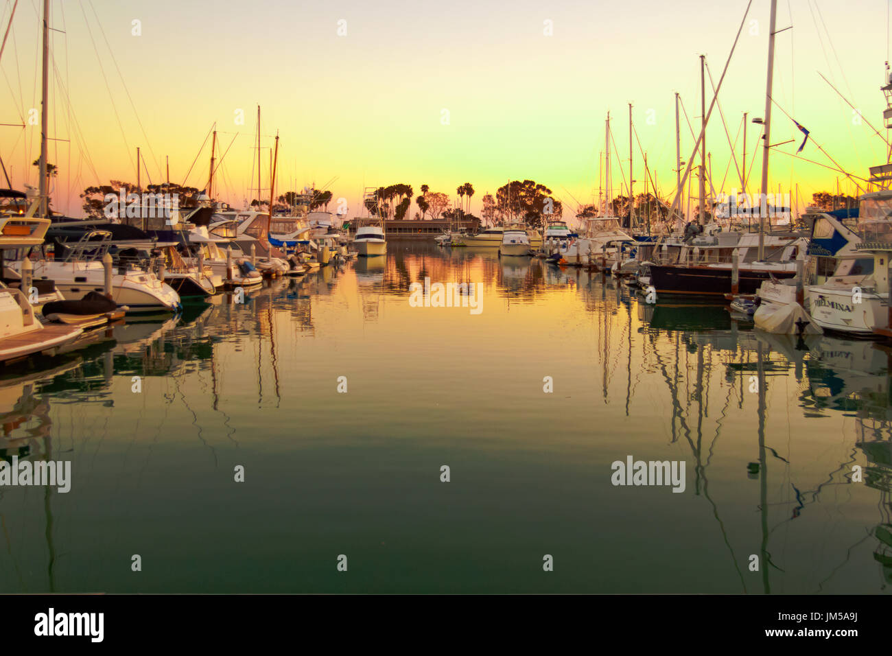 Dana Point Harbor,California, brilliant colors of the sunset, boats moored for the evening, reflections on the water - Stock Image