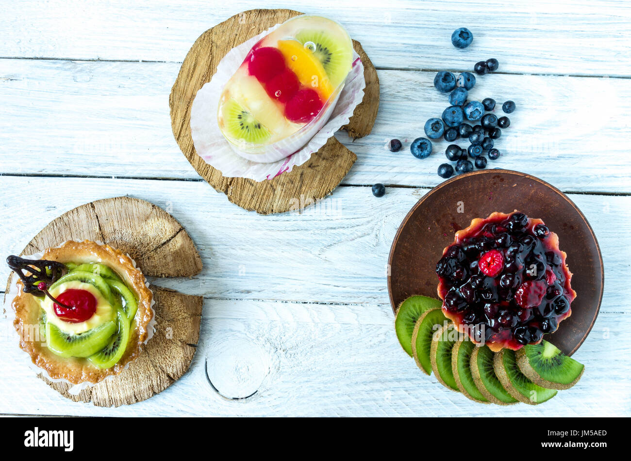 Three sweet pastries with fresh wild berries. Sweets on the table. - Stock Image
