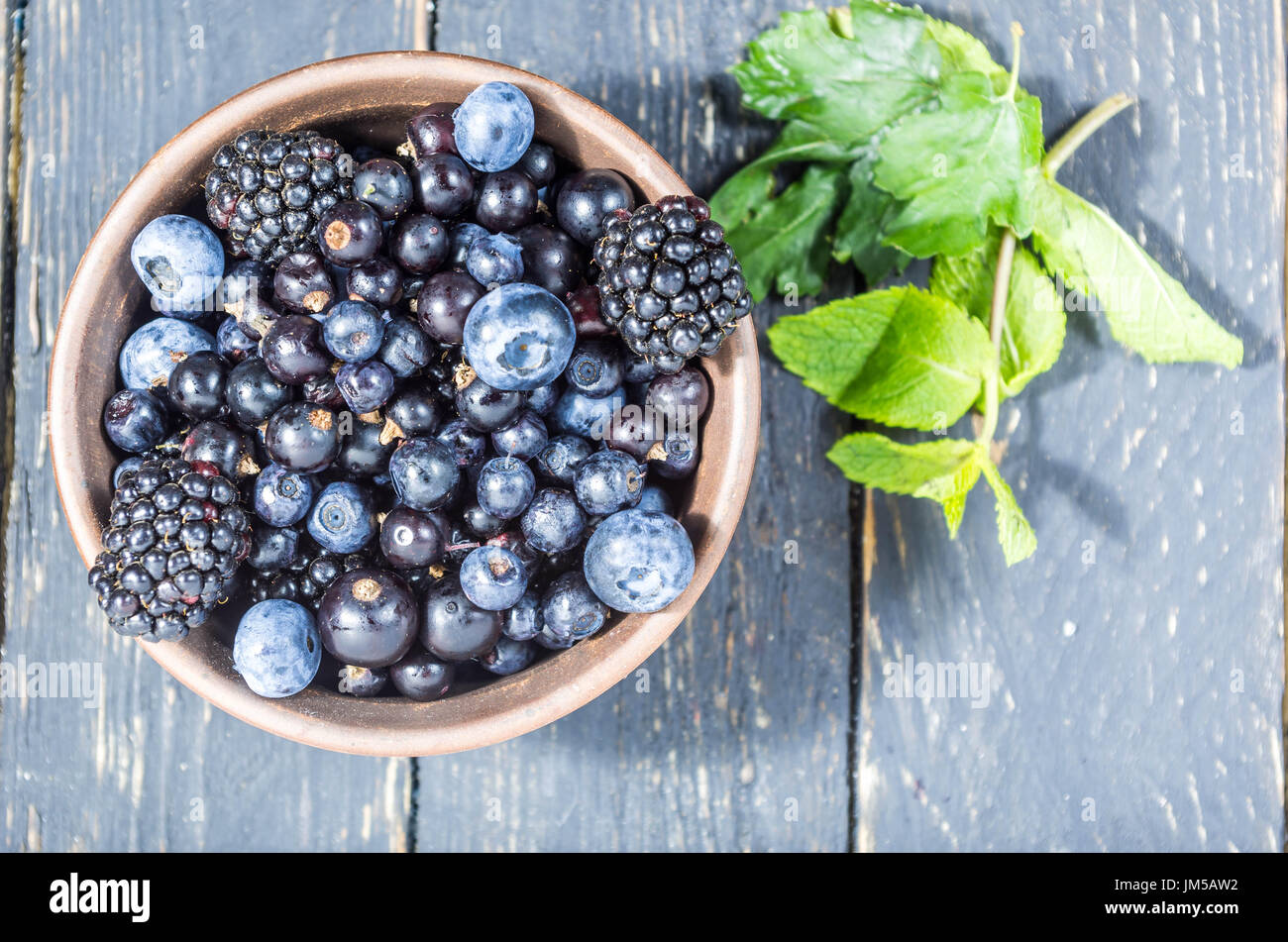 Forest berries in a clay plate. Low depth of field. Berry decoration. - Stock Image