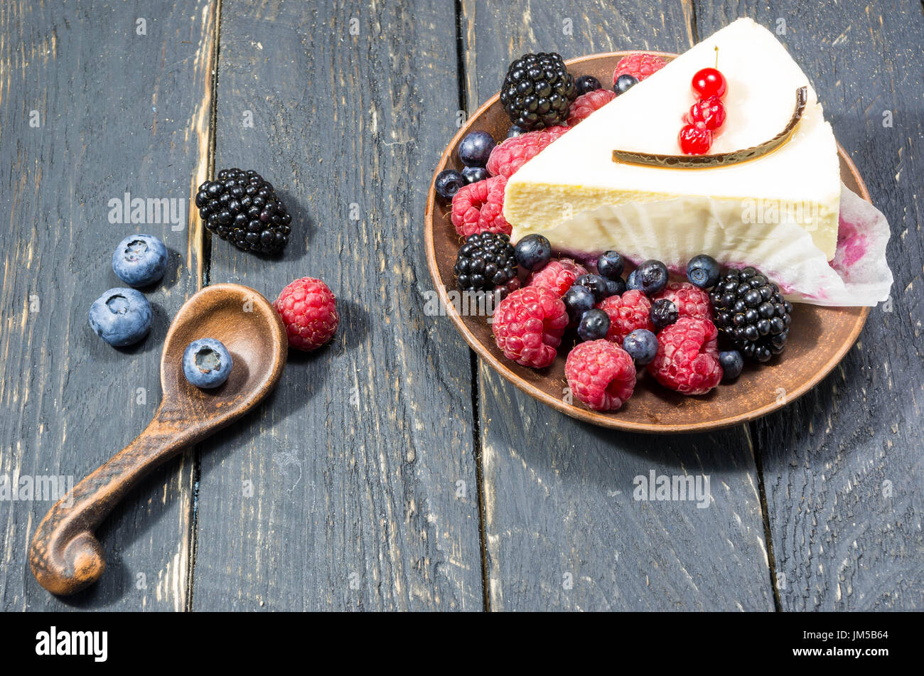 Dessert menu with berries in earthenware. Multicolored forest berries. - Stock Image