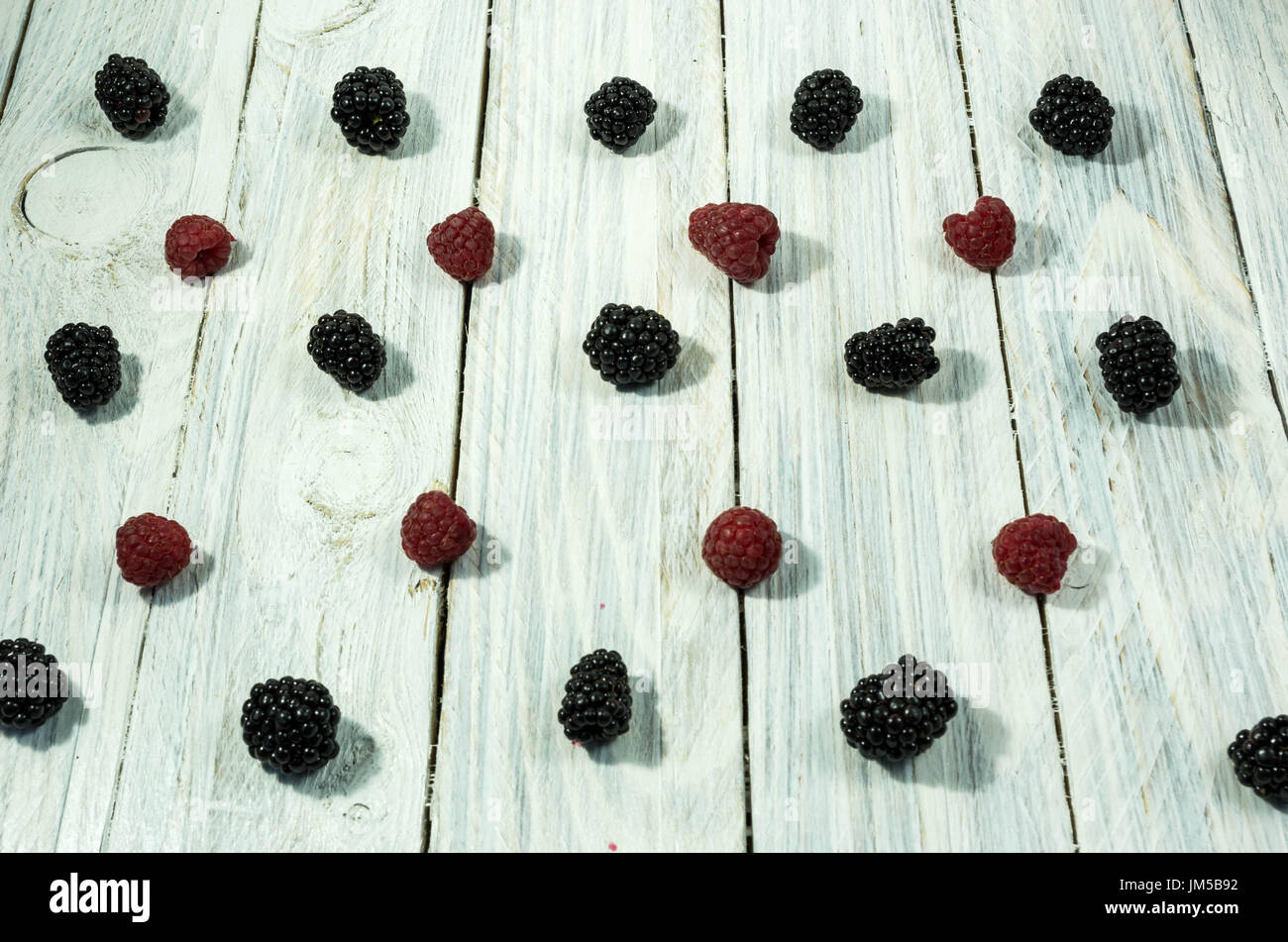 Blackberry and raspberries. are arranged in a row. Top view. Berries on a white background. - Stock Image