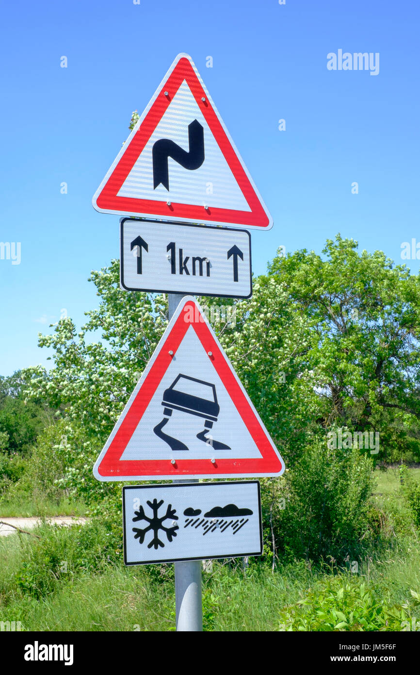 road sign warning of bends in road and slippery surface in snow or icy conditions zala county hungary - Stock Image