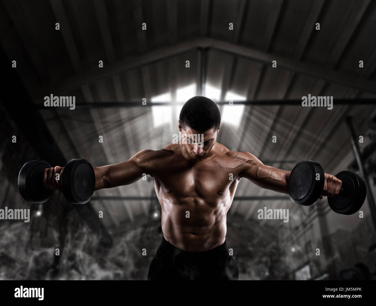 Athletic man training biceps at the gym - Stock Image