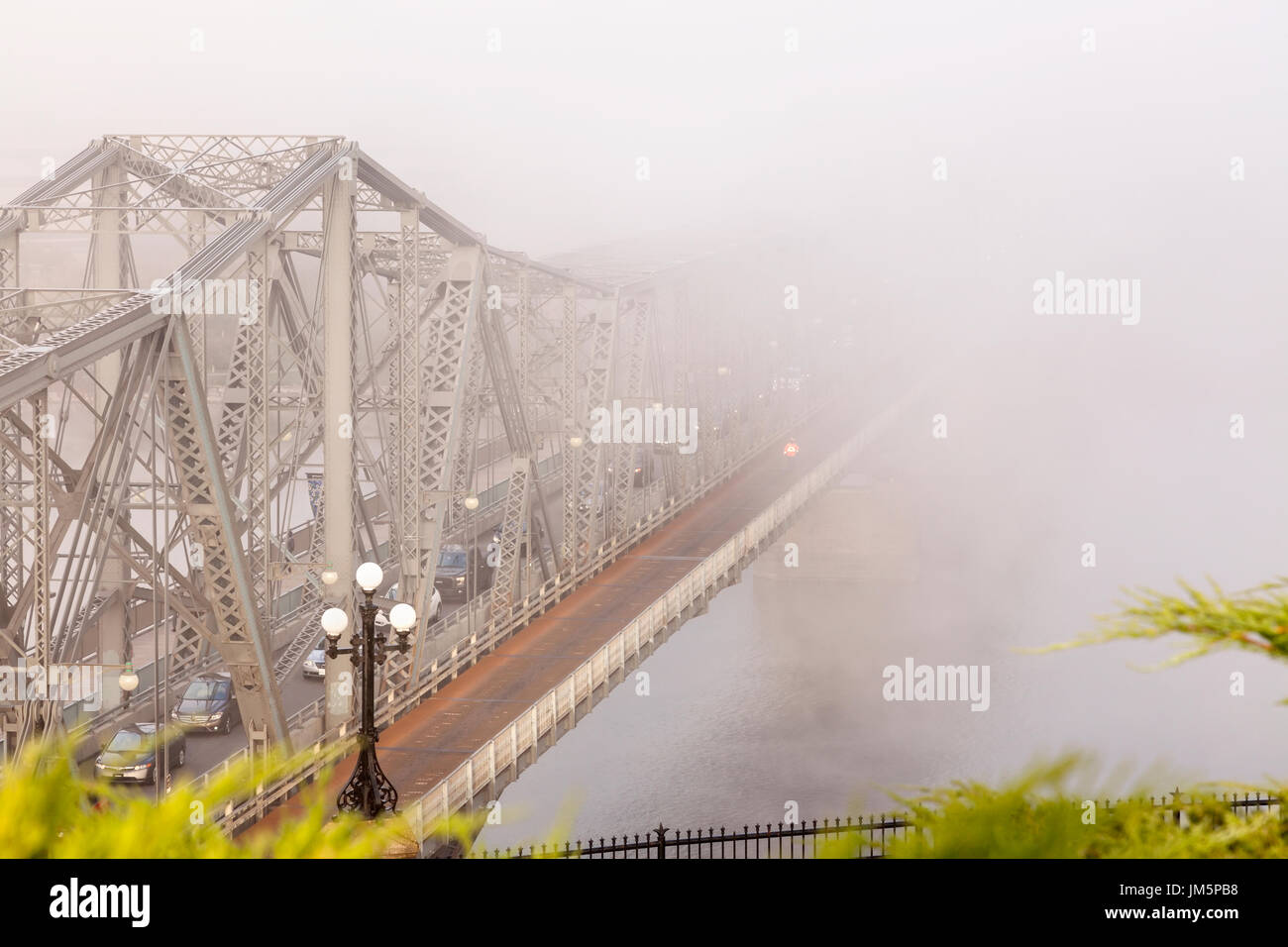 The Royal Alexandra Interprovincial Bridge is a steel truss cantilever bridge that spans the Ottawa River during a foggy morning in Ottawa, Ontario. - Stock Image