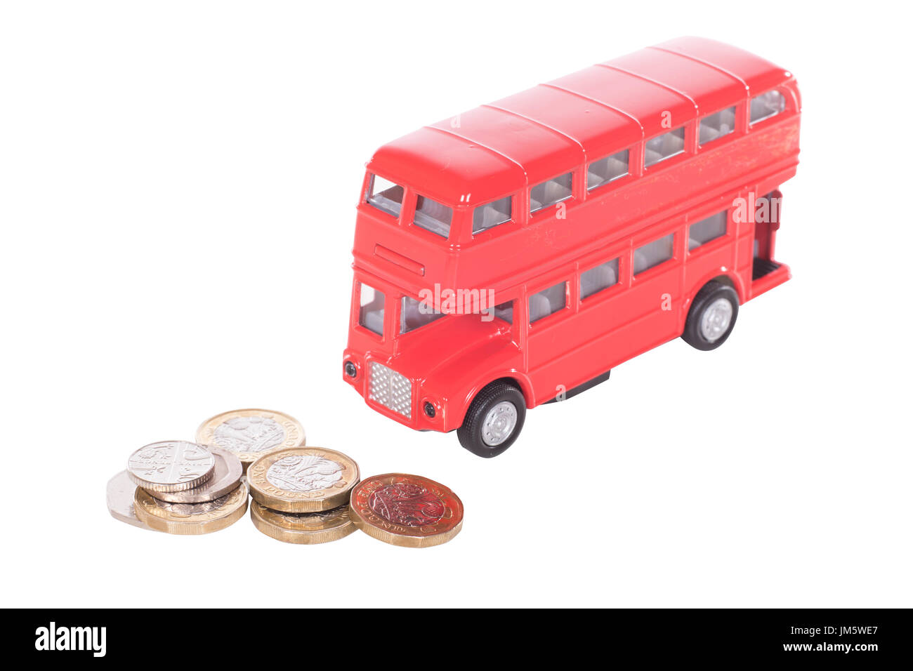 Pile of UK cash money in loose coins with a model red double-decker bus in a concept of the cost of public transport and commuting - Stock Image