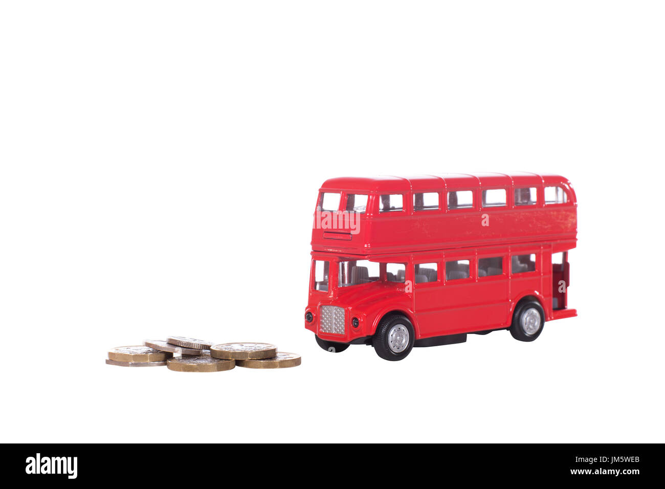 Cash coins with a model red double-decker bus symbolic of British transport and the cost of travelling isolated on white - Stock Image