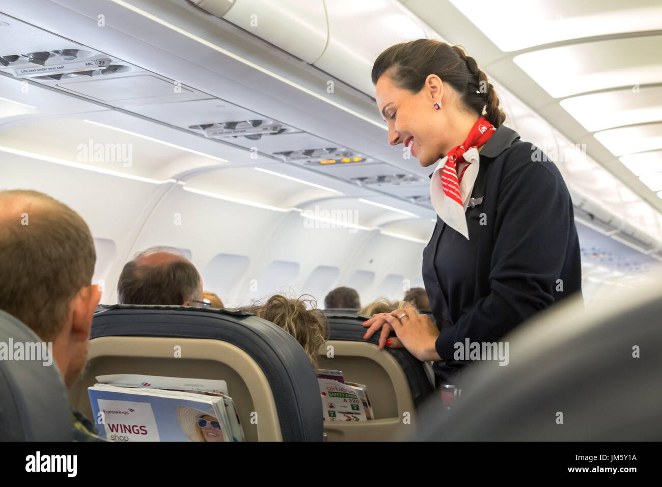 Thessaloniki , Greece - July 16, 2017: A female flight attendant  is speaking with a passenger sitting in the economy class. - Stock Image