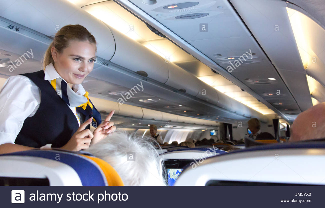 Munich, Germany - July 16, 2017:  A female flight attendant  is speaking with a passenger, economy class, Lufthansa Airlines. - Stock Image