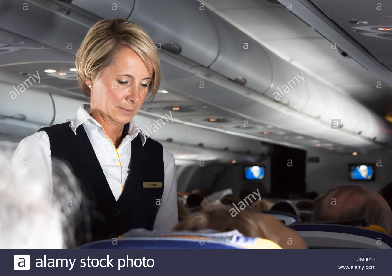 Munich, Germany - July 16, 2017:  A female flight attendant of Lufthansa Airlines is listening a request from a passenger. - Stock Image