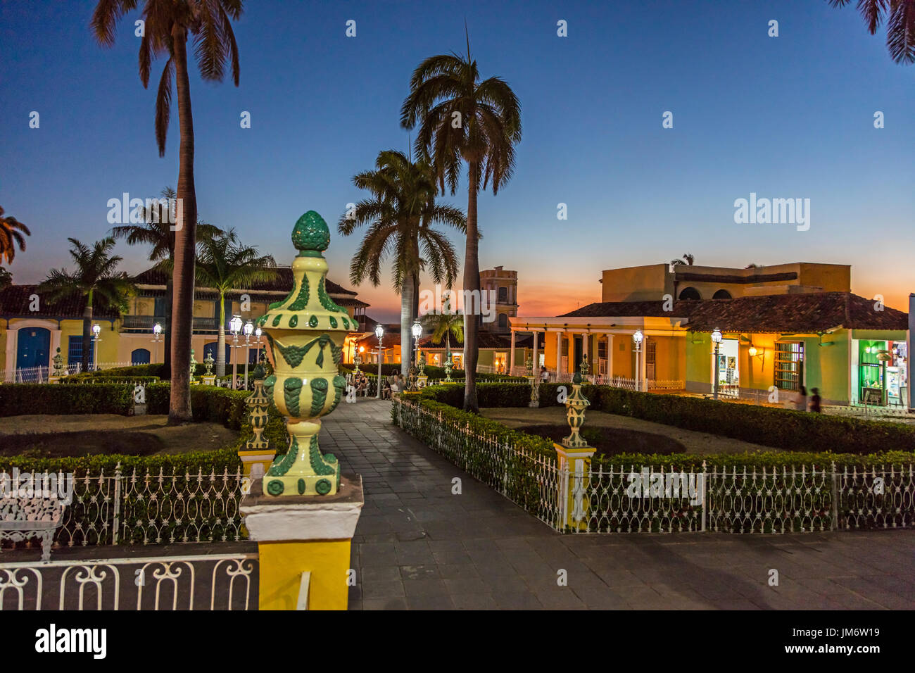 Palm trees and historic buildings on the PLAZA MAYOR at dusk - TRINIDAD, CUBA - Stock Image