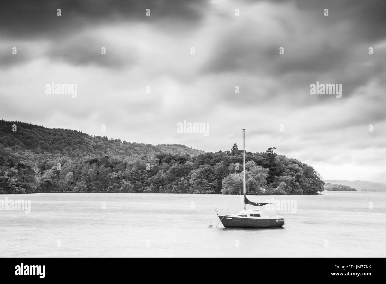 A sailing boat in a calming lake as storm is approaching. UK - Stock Image