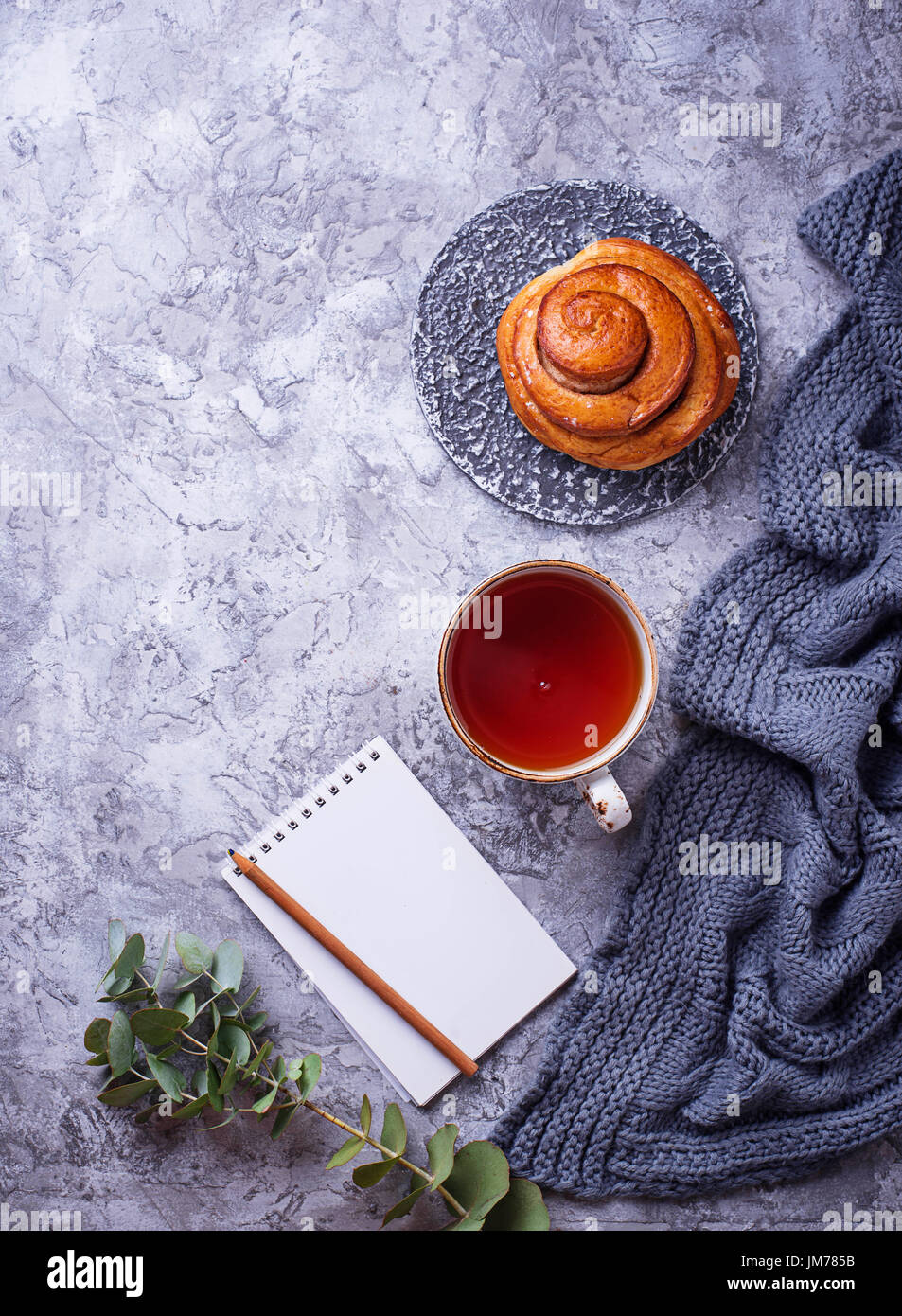 Feminine workspace with bun, cup of tea and notebook. Flat lay, top view - Stock Image