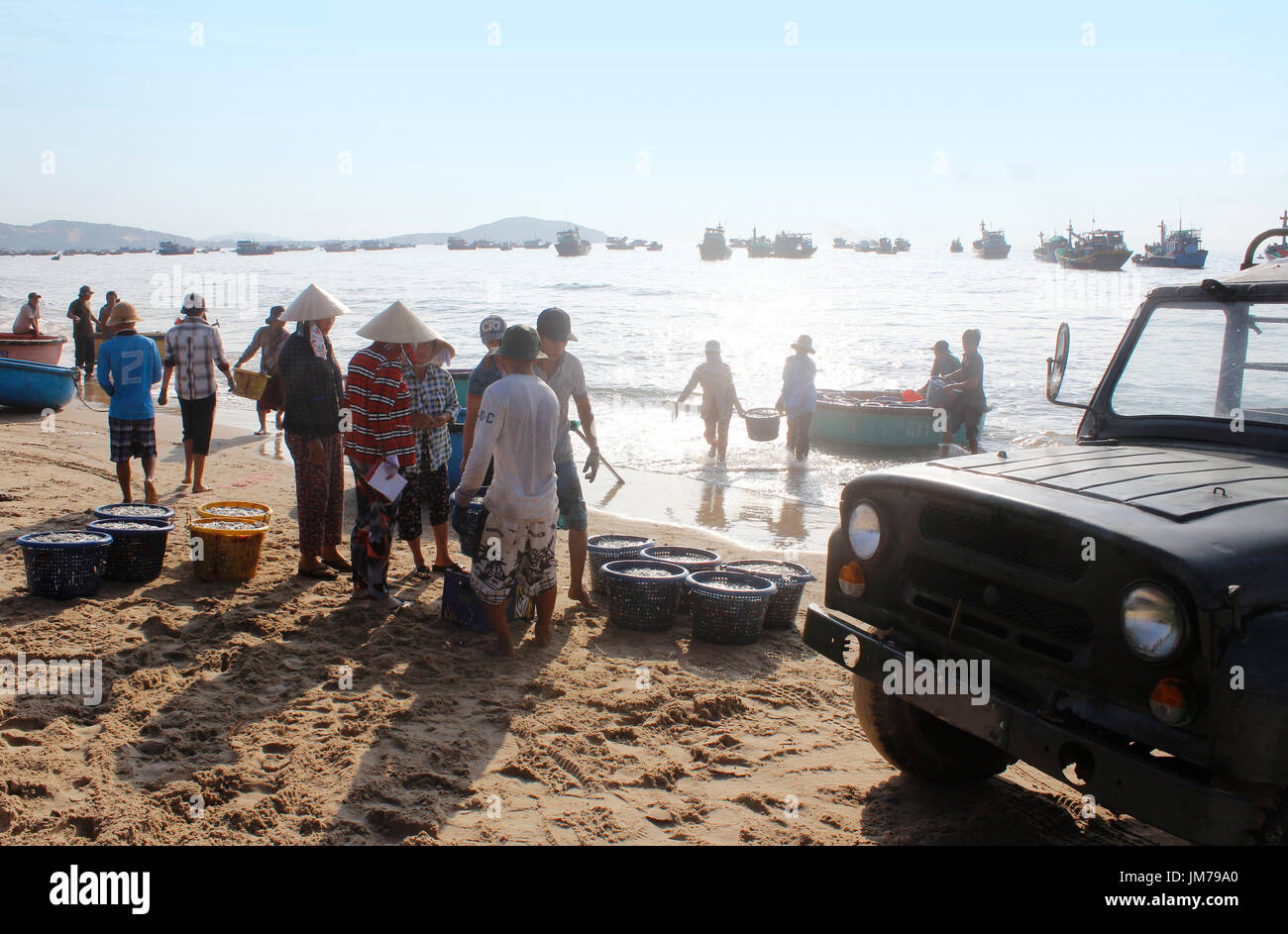 Mui Ne, Vietnam - June 27, 2017: Crowded scene of daily early morning fish market on beach with the fishermen carrying Stock Photo