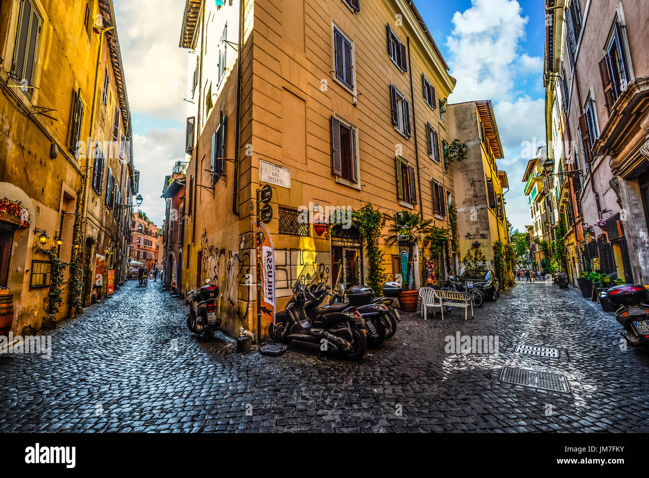 Picturesque and colorful back street with motorcycles and shops in the Trastevere district of Rome Italy on a sunny summer afternoon - Stock Image