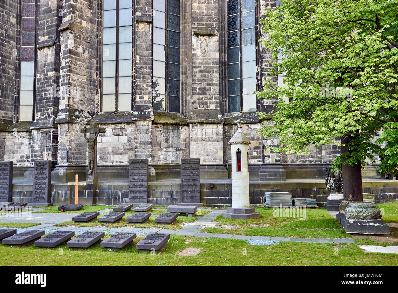 ancient gravesites marked by horizontal headstones at the foot of Cologne Cathedral - Stock Image