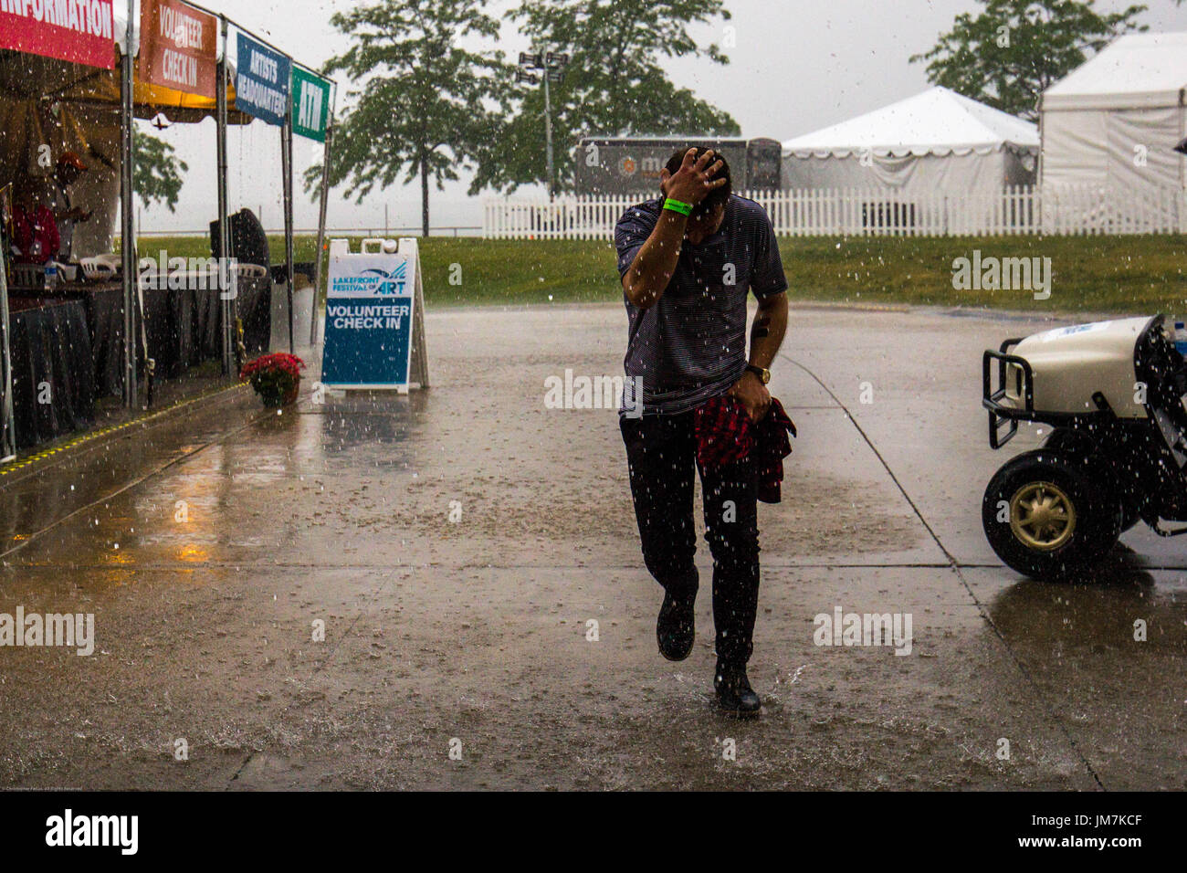 Running in from the rain with his hand on his head. - Stock Image