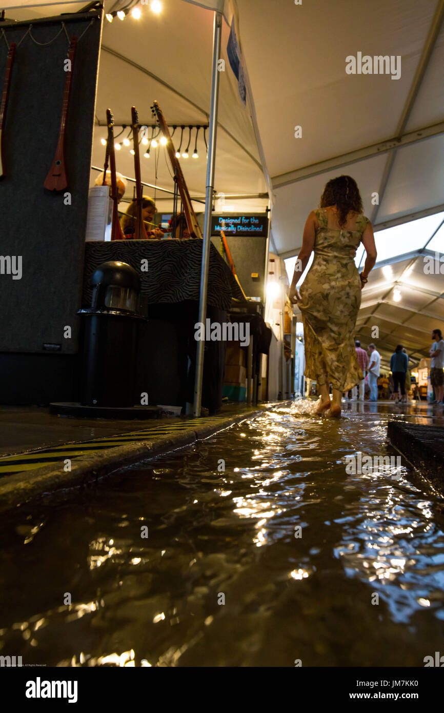 Woman dancing in a puddle. - Stock Image