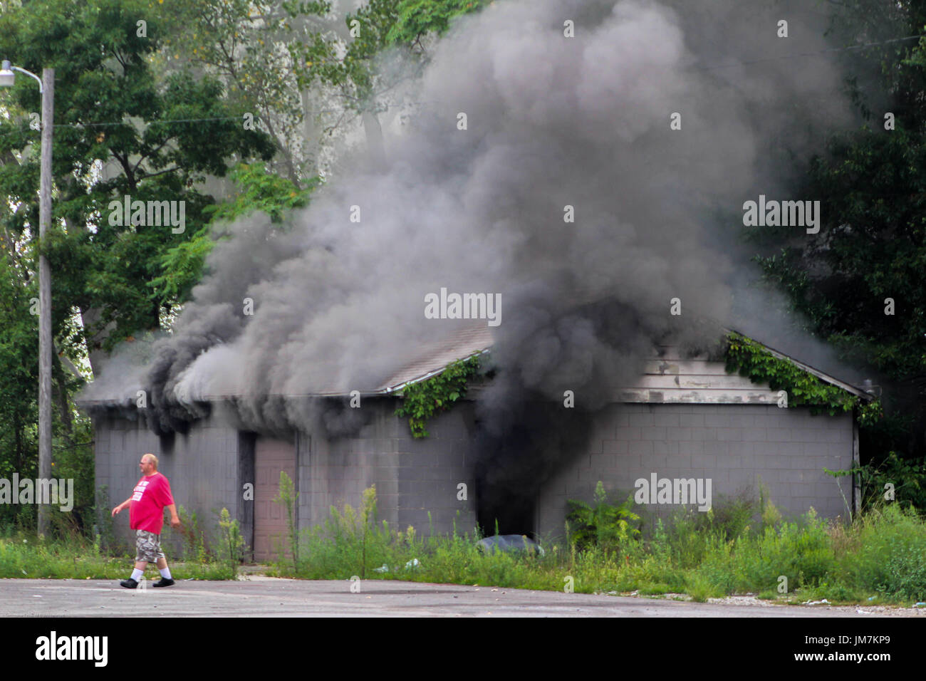 Man walks away from burning building. - Stock Image