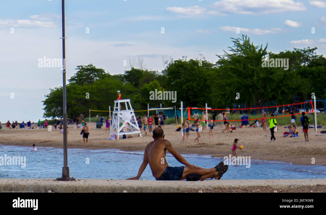Man tanning at the beach. - Stock Image