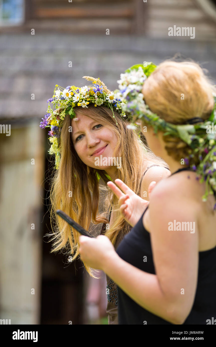 slavic girl with wrath on head talking to other woman and smiling to the camera - Stock Image
